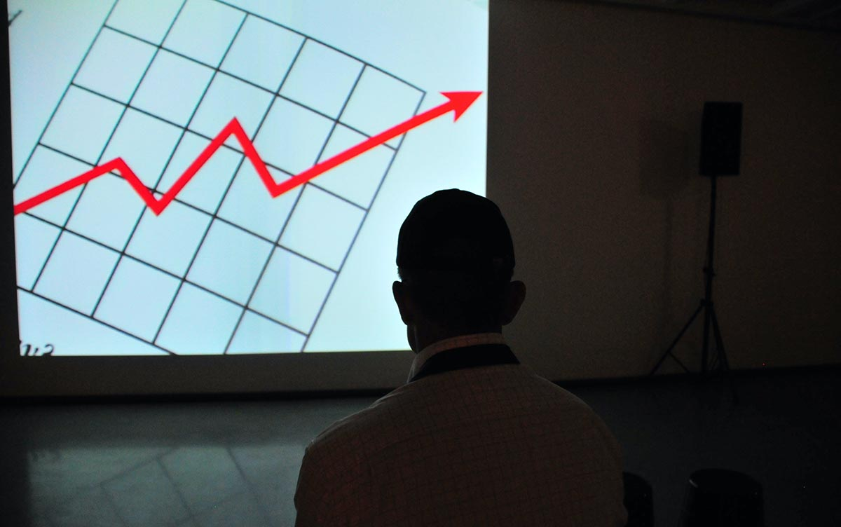 Man standing in dark room looking at graph projected on wall